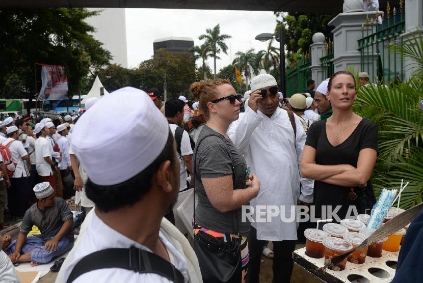 Dua wisatawan asing menonton Aksi Super Damai Bela Islam III di Monumen Nasional, Jakarta, Jumat (2/12).