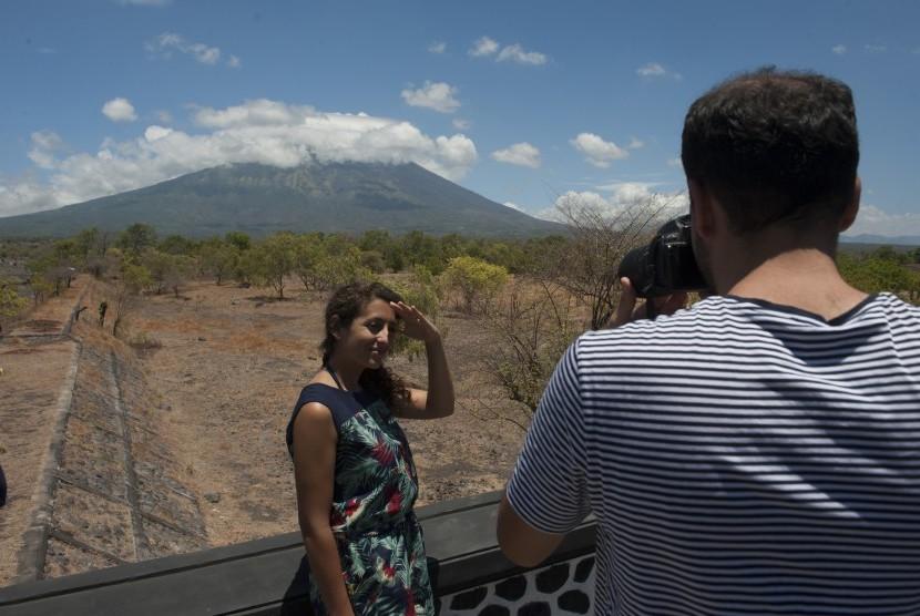 Dua wisatawan berfoto dengan latar belakang Gunung Agung, di Desa Batu Niti yang berjarak sekitar 12 kilometer dari gunung berstatus awas itu, Karangasem, Bali, Senin (25/9).