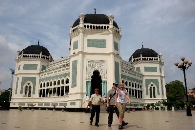 Dua wisatawan mancanegara bersama seorang pemandu ketika mengunjungi Masjid Raya Al-Mashun, Medan, Sumut, Selasa (5/6). Pihak Dinas Kebudayaan dan Pariwisata Kota Medan menyatakan, kunjungan wisatawan mancanegara ke Medan meningkat 20 persen dari bulan seb