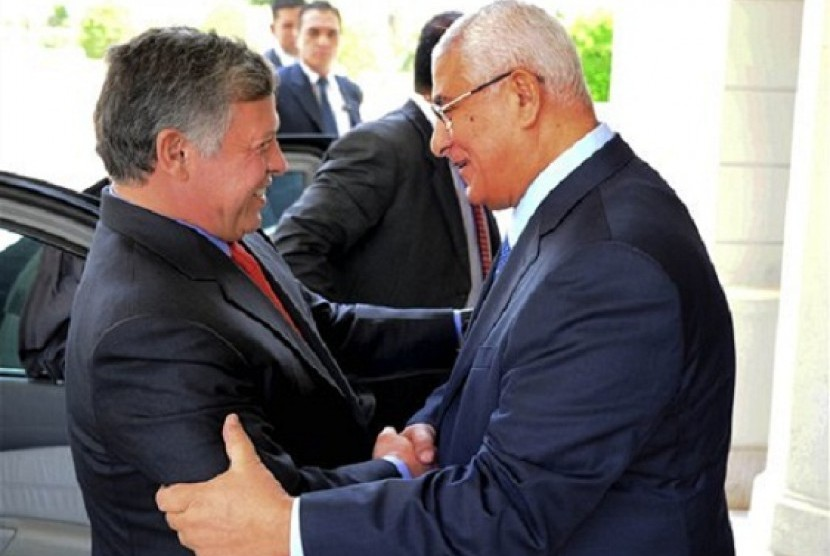 Egyptian President Adly Mansour (right) greets Jordan's King Abdullah II on his arrival to the presidential palace in Cairo, Saturday, July 20, 2013.