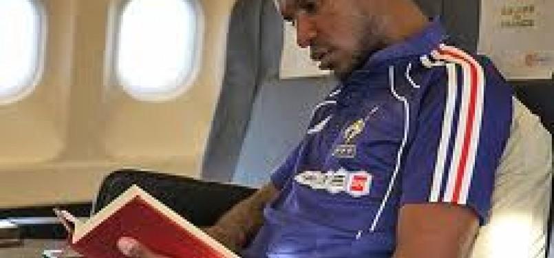 Eric 'Bilal' Abidal sedang membaca Alquran di dalam pesawat. Bek Barcelona itu dikabarkan bakal menjalani transplantasi hati dalam beberapa pekan ke depan.