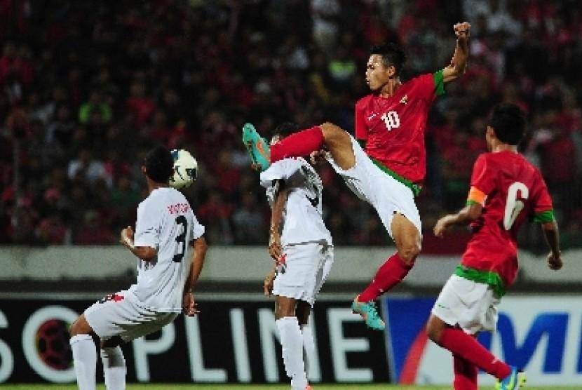 Pesepak bola tim nasional Indonesia, Muchlis Hadi (kedua kanan) berebut bola dengan pesepak bola timnas Timor Leste dalam pertandingan babak semifinal Piala AFF U-19 Championship 2013 di Gelora Delta Sidoarjo, Jatim, Jumat (20/9) malam.