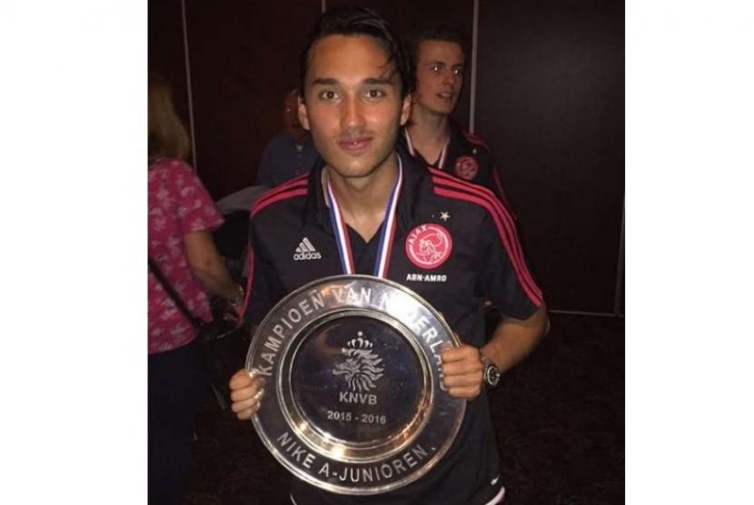 Ezra Walian memegang trofi juara kelompok remaja Belanda musim 2015/2016 bersama Ajax.