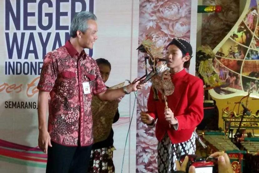 Foe Jose Amadeus Khrisna (memegang wayang) bersama dengan Gubernur Jawa Tengah, Ganjar Pranowo
