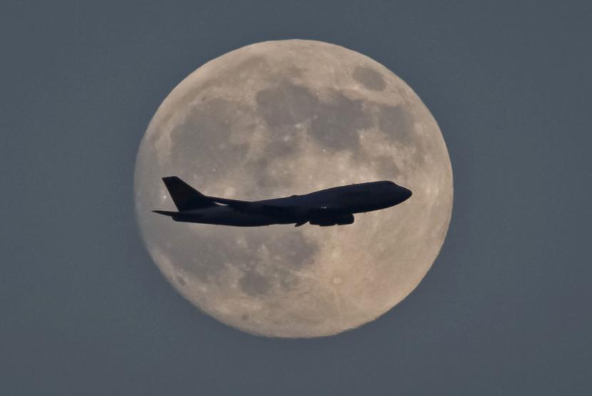 Foto siluet pesawat terbang melintas di udara dengan latar bulan purnama di Frankfurt. (EPA/Mumpenhorst)