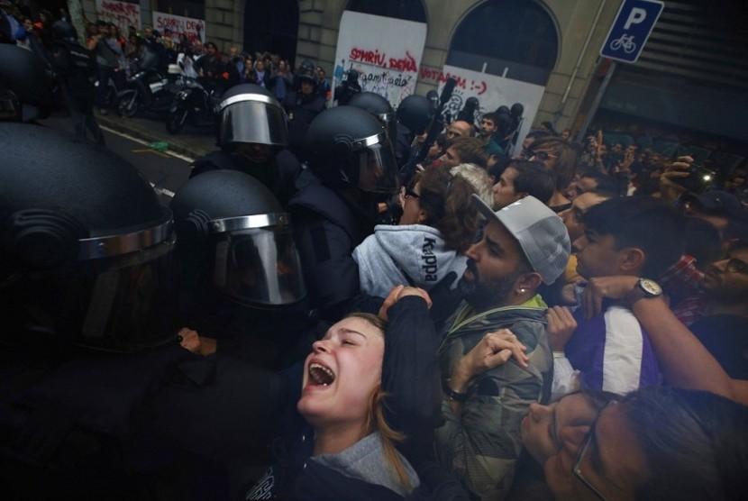 Foto yang diambil pada Minggu (1/10) memperlihatkan seorang gadis berteriak histeris kepada petugas Polisi Spanyol yang berusaha membubarkan para pendukung pro referendum kemerdekaan katalunya di luar gedung sekolah Ramon Llull di Barcelona.