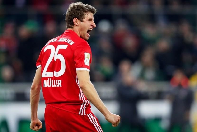 Gelandang Bayern Muenchen, Thomas Mueller merayakan golnya ke gawang Borussia Muenchengladbach, pada laga Bundesliga di Borussia-Park, Ahad (19/3). Muenchen menang 1-0.