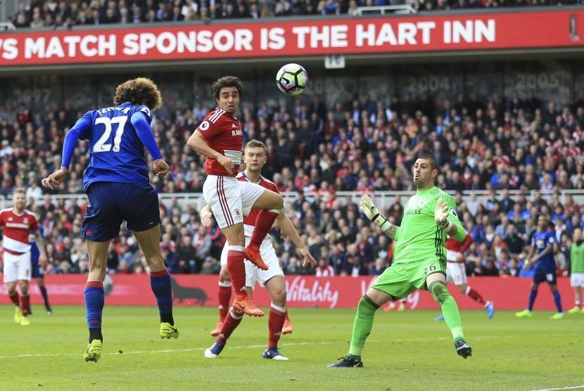 Gelandang Manchester United, Marouane Fellaini (kiri) menanduk bola masuk ke gawang Middlesbrough pada laga Liga Primer Inggris, di stadion Riverside, Ahad (19/3). United unggul 1-0 pada babak pertama.