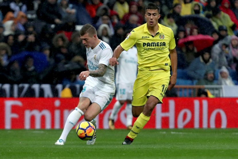 Gelandang Real Madrid Toni Kroos (kiri) berebut bola dengan gelandang Villarreal Rodrigo Hernandez 'Rodri' (kanan) pada lanjutan La Liga di Stadion Santiago Bernabeu, Ahad (14/1) dini hari WIB.