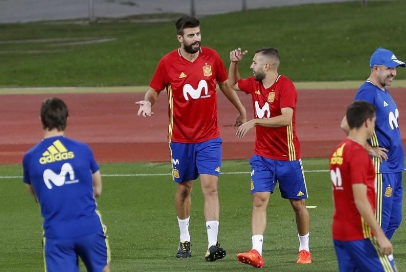 Gerard Pique (kedua kiri) bercengkrama dengan Jordi Alba dalam latihan timnas Spanyol di Las Rozas, Madrid, Senin (2/10).