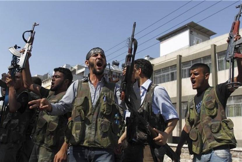 Gerilyawan anggota Pasukan Pembebasan Suriah (FSA) meneriakan slogan ketik mereka bersiap bergerak menuju distrik Salah Edinne, Aleppo, Suriah, pada Kamis (9/8).