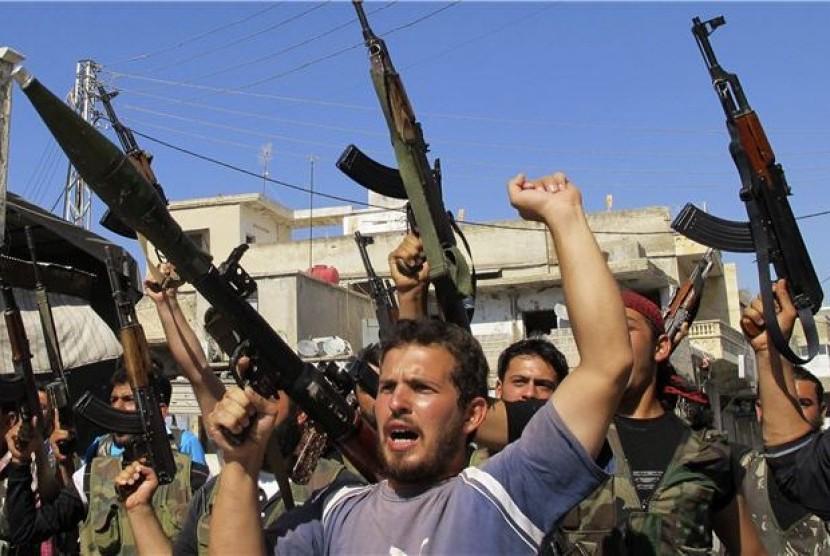 Gerilyawan anggota Tentara Pembebasan Suriah melontarkan kecaman menentang Presiden Suriah, Bashar Al Assad, di Azzaz, Aleppo, Suriah.
