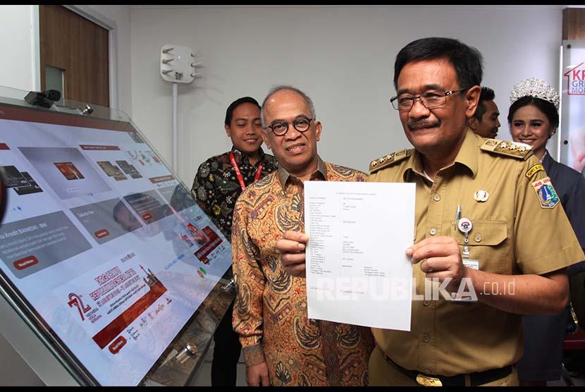 Gubernur DKI Jakarta Djarot Saiful Hidayat (kanan) melakukan transaksi pembayaran s