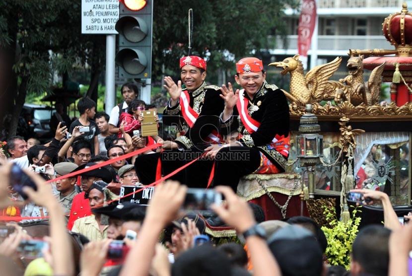 Gubernur DKI Jakarta Joko Widodo dan Wakil Gubernur Basuki Tjahaja Purnama menyapa warga diatas kereta kencana saat mengikuti kirab di Jalan Medan merdeka Barat, Jakarta, Ahad (8/12).  (Republika/Yasin Habibi)