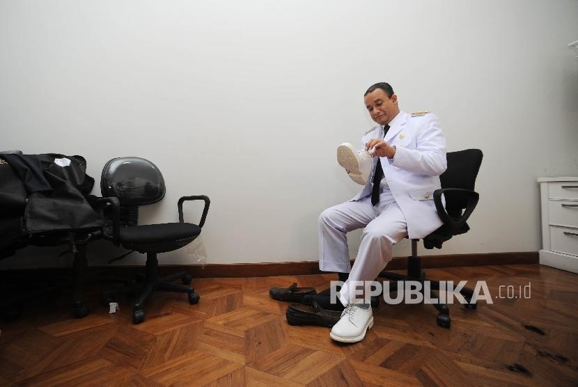 Gubernur DKI Jakarta terpilih Anies Baswedan memakai sepatu untuk melakukan sesi fitting dan foto pakaian dinas di Kebayoran Baru, Jakarta Selatan, Kamis (12/10).