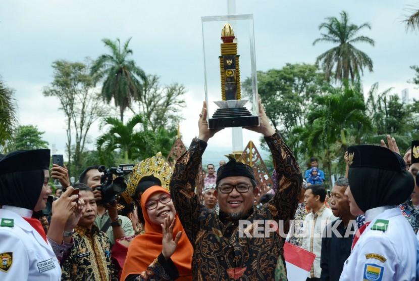 Gubernur Jawa Barat Ahmad Heryawan didampingi istri mengangkat penghargaan Parasamya Purnakarya Nugraha dari Presiden Republik Indonesia atas prestasi kinerja tertinggi secara nasional, di depan Gedung Sate, Kota Bandung, Kamis (26/4).