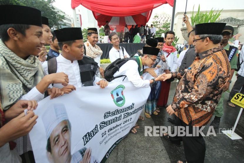 Gubernur Jawa Barat Ahmad Heryawan menyapa para santri usai peringatan Hari Santri Nasional 2017 Tingkat Jawa Barat, di halaman Masjid Raya Provinsi Jawa Barat, Alun-alun Kota Bandung, Kamis (26/10).