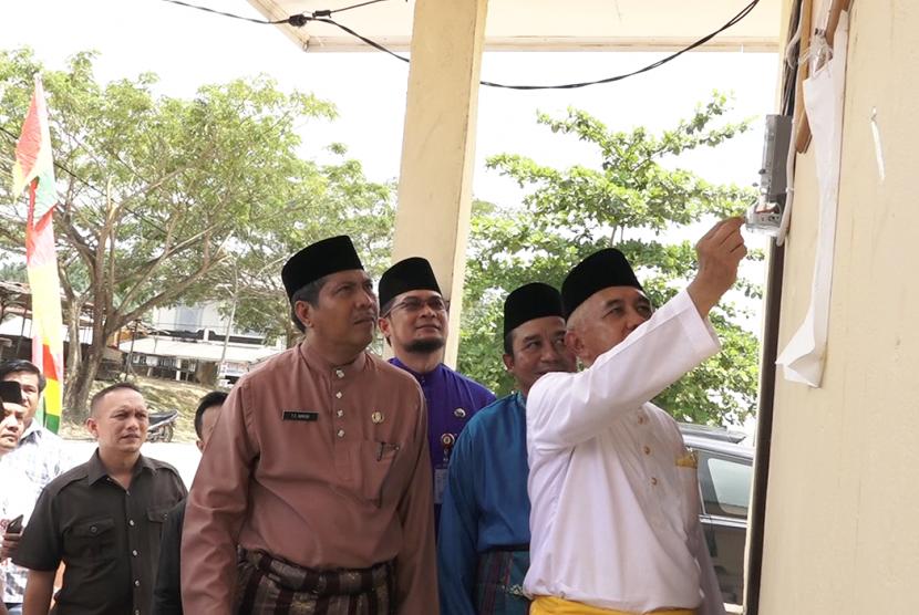 Gubernur Riau Arsyadjuliandi Rachman (kanan) menyalakan MCB di Pos Jaga Pasar Kuala Gasib, Kabupaten Siak Sri Indrapura, Jumat (27/10).