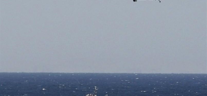 Helikopter angkatan laut AS terbang rendah di atas kapal perusak, Sterett, saat melintasi Selat Hormuz