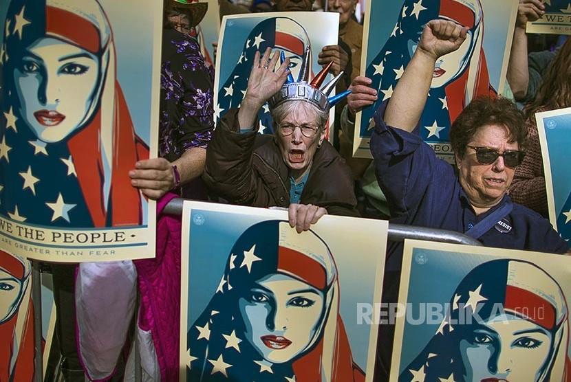 I am a Muslim Too: Pengunjukrasa membawa poster bergambar wanita berhijab bendera Amerika di sela unjuk rasa menolak kebijakan Anti Imigran Trump di Lapang Times Square New York, AS, (19/2) waktu setempat.