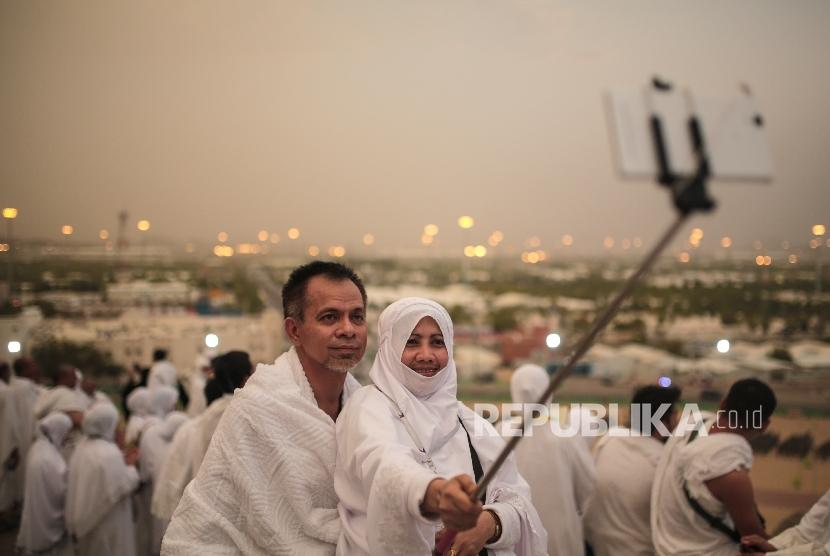 Ilustrasi jamaah melakukan foto selfie saat memakai pakaian umrah.