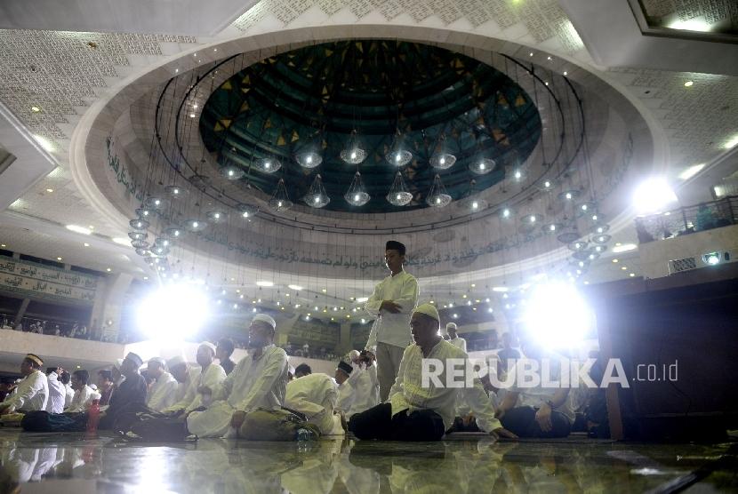 Jamaah mengikuti Shalat Isya sebelum acara puncak Dzikir Nasional 2016 di Masjid At-Tin, Jakarta, Sabtu (31/12).