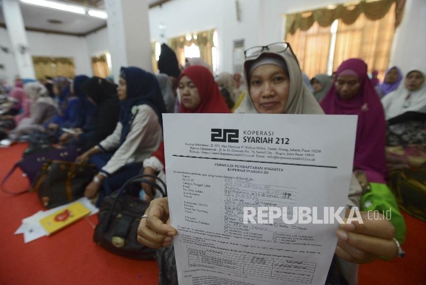 Jamaah menunjukan formulir untuk menjadi anggota koperasi syariah 212 yang telah diisi di STEI Tazkia, Bogor, Jawa Barat, Jumat (20/1).