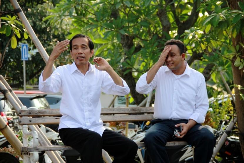 Joko Widodo (kiri) dan Juru Bicara Tim Pemenangan Pasangan Jokowi - JK, Anies Baswedan (kanan) duduk di bangku taman ketika berkunjung ke Taman Waduk Pluit di Jakarta Utara, Selasa (22/7).