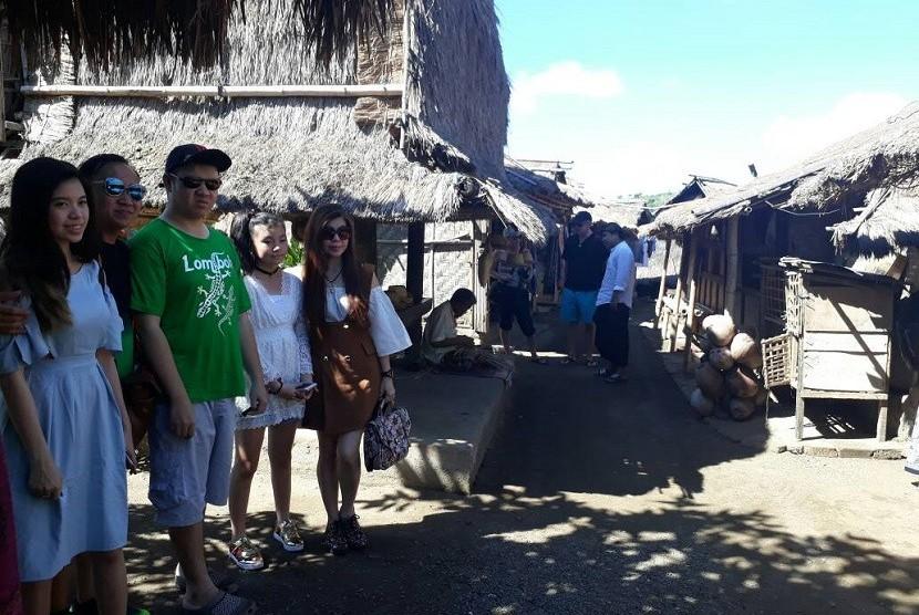 Kampung adat Sade di Dusun Sade, Desa Rembitan, Kecamatan Pujut, Kabupaten Lombok Tengah, NTB, ramai dikunjungi wisatawan saat liburan lebaran, Selasa (27/6). Tercatat lebih dari seribu orang berkunjung ke kampung adat tertua di selatan Pulau Lombok setiap hari selama liburan lebaran.