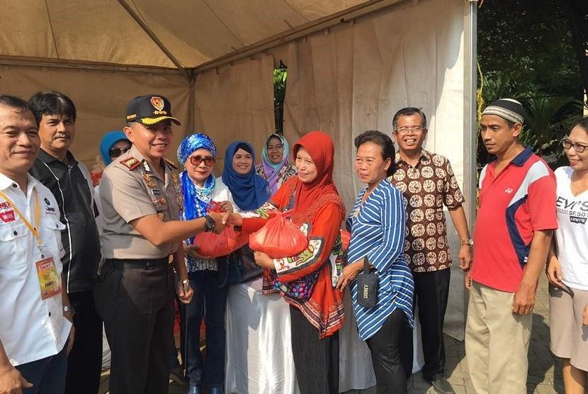 Kapolres Jakarta Timur Kombes Pol Andry Wibowo memberikan secara simbolis paket santunan anak yatim pada acara bazaar amal umat