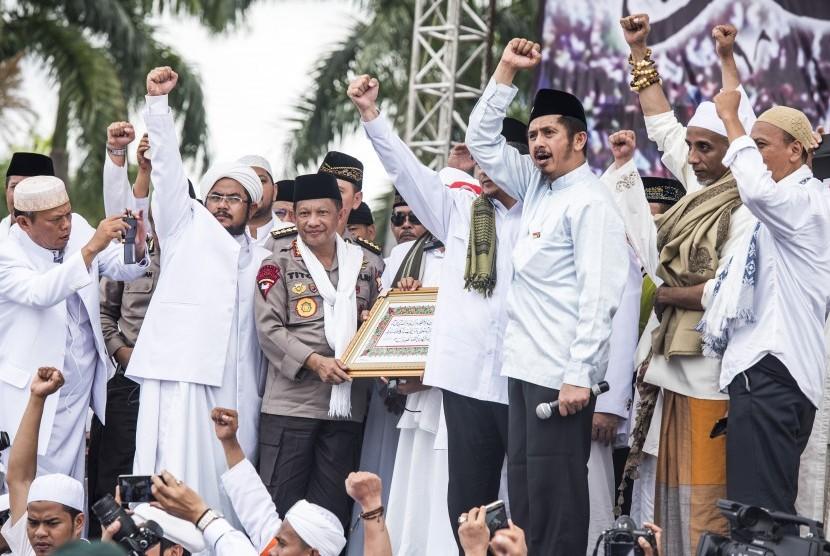 Kapolri Jenderal Pol Tito Karnavian (ketiga kiri) menerima kaligrafi dari ulama saat zikir dan berdoa bersama di kawasan silang Monas, Jakarta, Jumat (2/12).