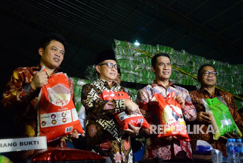 Kapolri Jenderal Tito Karnavian (kedua kiri) bersama Menteri Pertanian Amran Sulaiman (kedua kanan), Ketua Komisi Pengawas Persaiangan Usaha (KPPU) Syarkawi Rauf (kiri) dan Sekjen Kementerian Perdagangan Karyanto (kanan) menunjukkan karung berisi beras yang dipalsukan kandungan karbohidratnya dari berbagai merk saat penggerebekan gudang beras di PT Indo Beras Unggul, di kawasan Kedungwaringin, Kabupaten Bekasi, Jawa Barat, Kamis (20/7) malam.