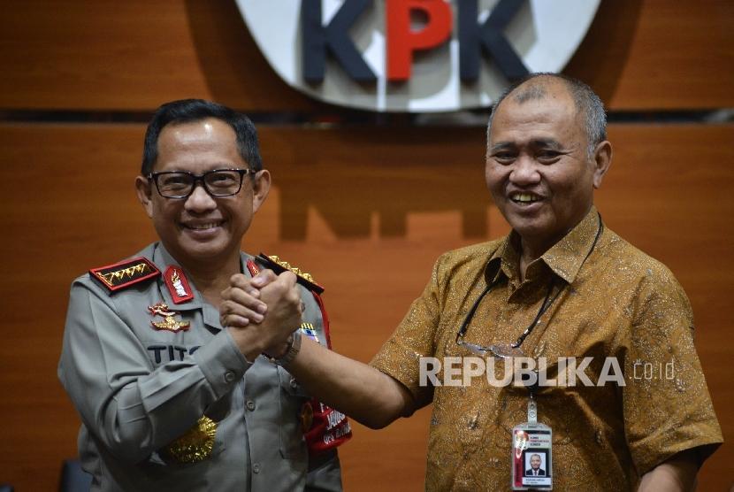 Kapolri Jenderal Tito Karnavian (kiri) bersalaman dengan Ketua KPK Agus Rahardjo (kanan) seusai memberikan keterangan kepada awak media saat mengunjungi pimpinan KPK di Gedung Merah Putih KPK, Jakarta, Senin (19/6).