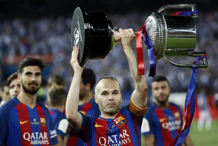 Kapten Barcelona, Andreas Iniesta mengangkat trofi Copa del Rey setelah timnya mengalahkan Deportivo Alaves, di Vicente Calderon, Ahad (28/5) dini hari WIB.