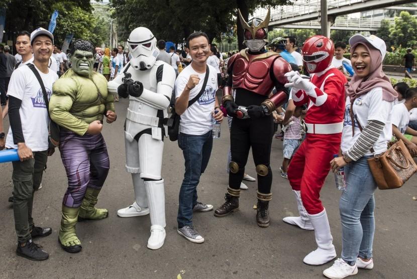 Karyawan bank BJB berfoto dengan tokoh komik saat Family Fun Walk HUT ke-56 bank BJB di Jakarta, Minggu (14/5).
