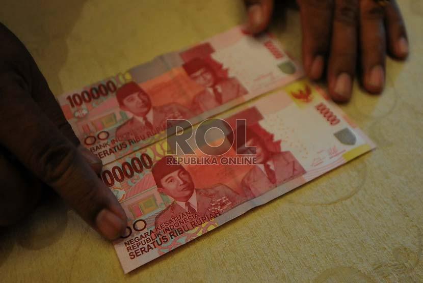 Karyawan Bank Indonesia memerlihatkan uang kertas pecahan Rp. 100.000 baru (atas) dan lama (bawah) usai launching uang tersebut di Bank Indonesia,Jakarta, Senin (18/8). (Republika/Prayogi)