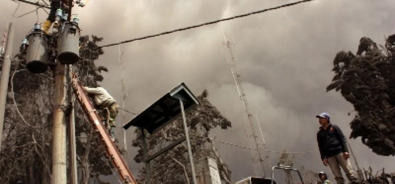 Karyawan PLN memperbaiki jaringan listrik.
