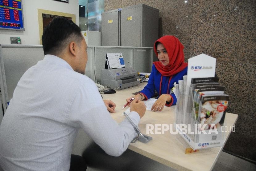 Karyawati melayani nasabah di Banking Hall Bank BTN, Jakarta, kamis (30/3).