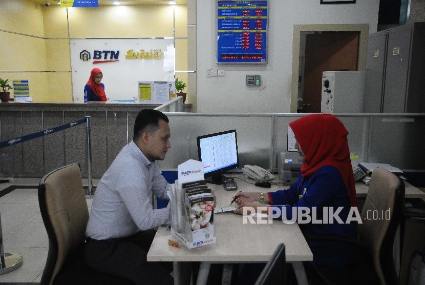 Karyawati melayani nasabah di Banking Hall Bank BTN, Jakarta.