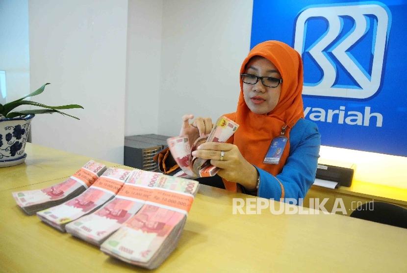 Karyawati menghitung uang di Banking Hall Bank BRI Syariah, Jakarta.