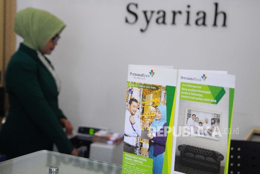 Karyawati menghitung uang di Banking hall Bank Permata Syariah, Jakarta, Selasa (14/3).