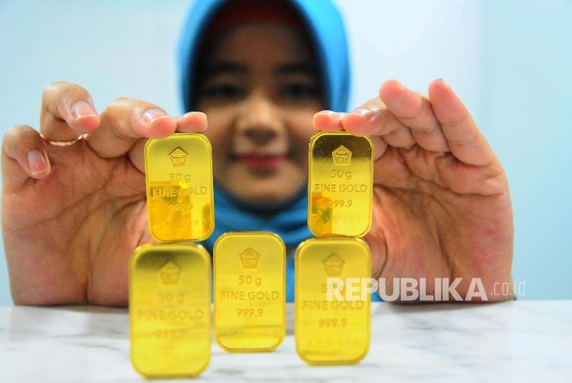 Karyawati menunjukan emas batangan di Banking Hall Bank BNI Syariah, Jakarta, Selasa (23/5).