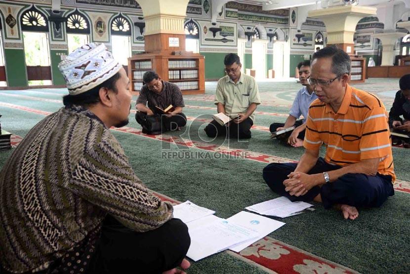 Ketua Lembaga Tahfizh Al-Azhar, Achmad Khotib (kiri) membimbing jamaah peserta Program Hafalan Alquran di Masjid Al-Azhar, Jakarta, Ahad (9/6).  (Republika/Agung Supriyanto)