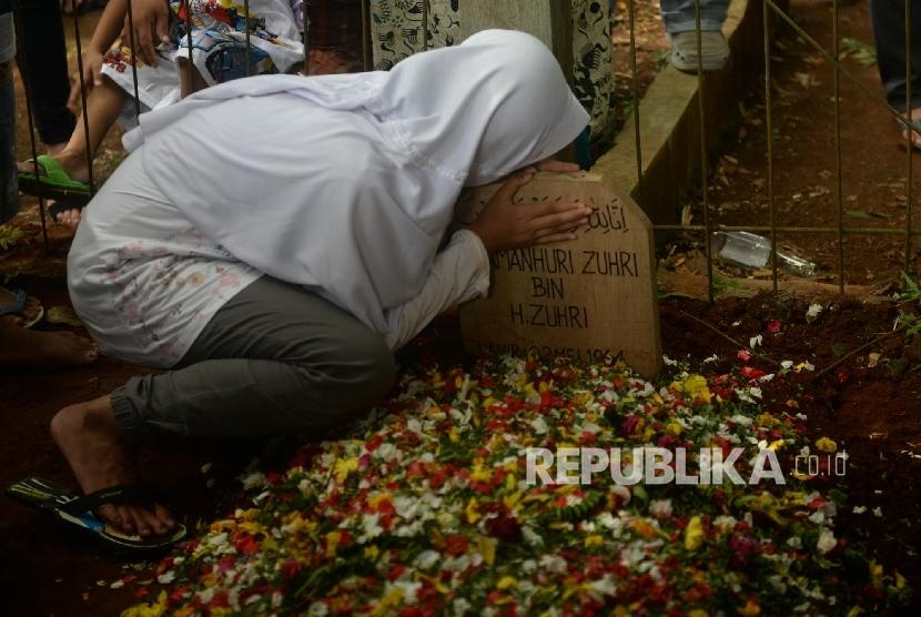 Keluarga Almarhum Damanhuri Zuhri mencium pusara usai pemakaman di Parung, Bogor, Jawa Barat, Senin (2/1). Kang Daman meninggal akibat penyakit pada Senin (2/1) pagi.