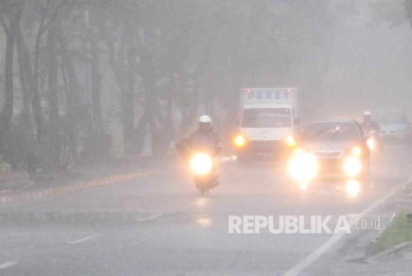 Pengendara menyalakan lampu karena pendeknya jarak pandang saat hujan deras yang mengguyur Kota Bandung, di Jalan Supratman, Kamis (16/11) siang. Derasnya hujan menyebabkan sejumlah ruas jalan di Kota Bandung digenang banjir dari luapan drainase.