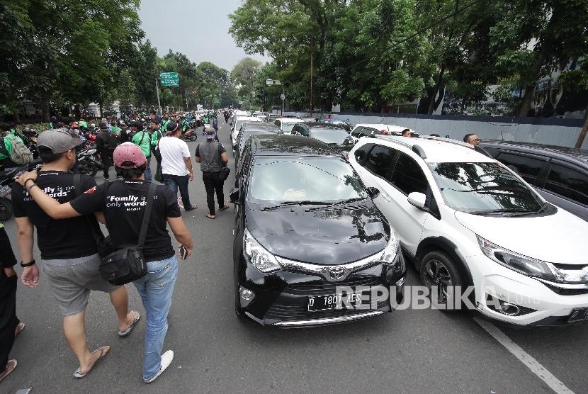 Kendaraan taksi online diparkir di Jl Diponegoro saat aksi ribuan pengemudi trasportasi berbasisi aplikasi online di depan Gedung Sate, Kota Bandung, Senin (16/10).