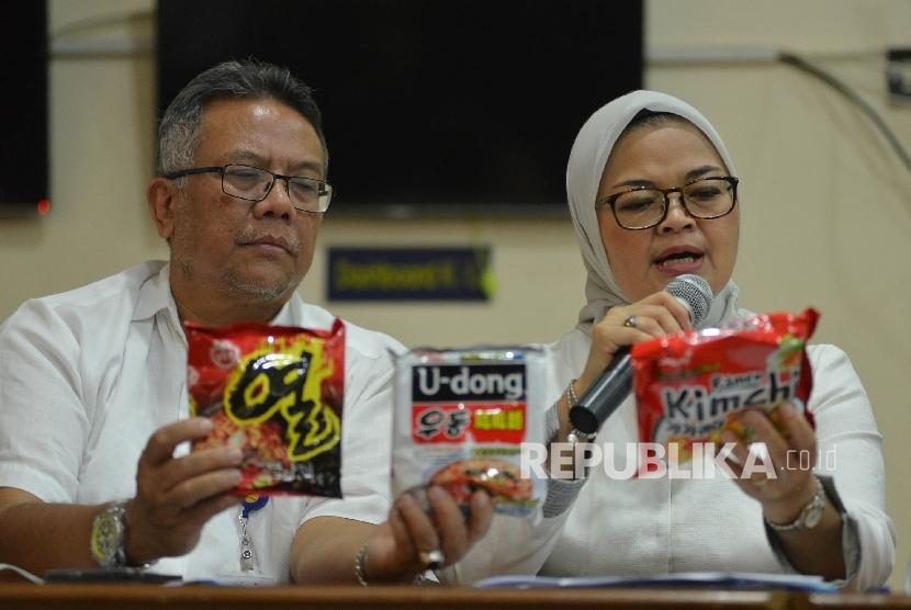 Kepala Badan Pengawan Obat dan Makanan (BPOM) Penny Kusumastuti Lukito (kanan) bersama Deputi Bidang Pengawasan Keamanan Pangan dan Bahan Berbahaya Suratmono (kiri) menunjukan mi yang mengandung minyak babi saat menggelar konferensi pers di Pelabuhan Tanjung Priok, Jakarta Utara, Senin (19/6).