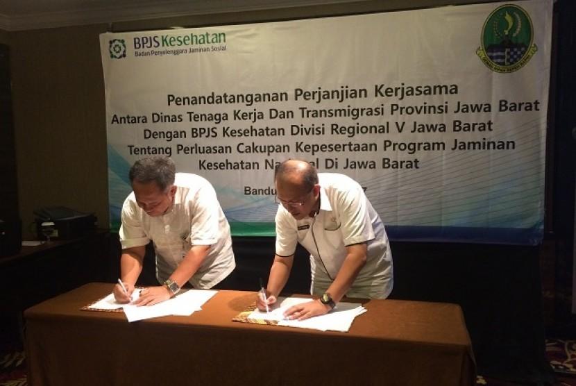 Kepala BPJS Kesehatan Divisi Regional V Jawa Barat Mohammad Edison (kiri) menandatangani kesepakatan kerja dengan Kepala Dinas Tenaga Kerja dan Transmigrasi Provinsi Jawa Barat Ferry Sofwan Arif di Kota Bandung, Rabu (19/4).