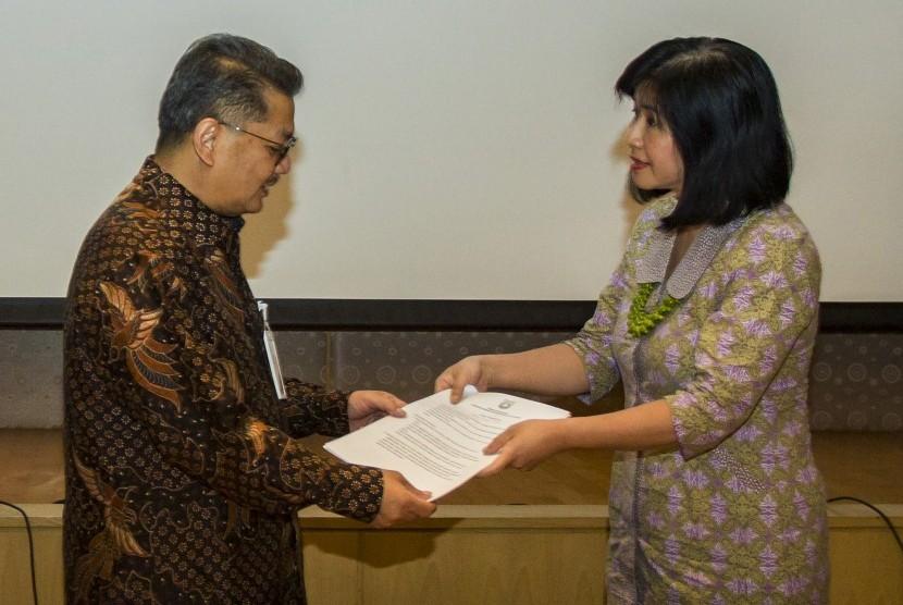 Kepala Dinas Kesehatan DKI Jakarta Koesmedi Priharto (kiri) memberikan surat peringatan tertulis kepada Direktur RS Mitra Keluarga Kalideres Francisca Dewi (kanan) saat pertemuan Kepala Dinas Kesehatan dengan seluruh Direktur Rumah Sakit se-DKI Jakarta di Kantor Dinas Kesehatan DKI Jakarta, Jakarta, Jumat (15/9).