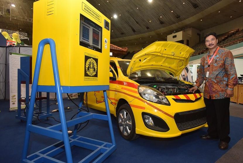 Kepala Laboratorium Teknik Kendali Fakultas Teknik Universitas Indonesia (UI) Feri Yusivar berpose di depan mobil listrik hasil inovasi dan karya dari dosen dan mahasiswa UI yang dipamerkan pada acara Seminar dan Pameran Ketenagalistrikan di Jakarta